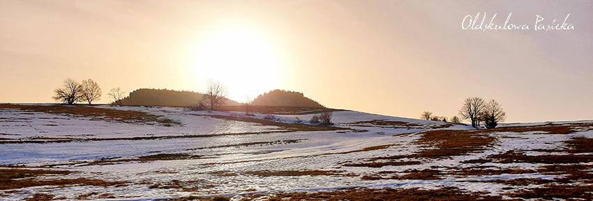 Widok na szczyty dwóch Szczelińców Wielkiego i Małego z łąk. Łąki częściowo jeszcze zaśnieżone. Pomiędzy szczytami wschodzi słońce. Ciepły lutowy dzień.