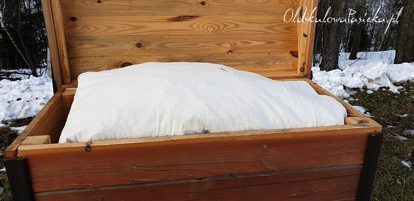 Otwarty daszek ula a w nim położona na ramkach poduszka wypchana słomą służąca do docieplenia rodziny pszczelej.